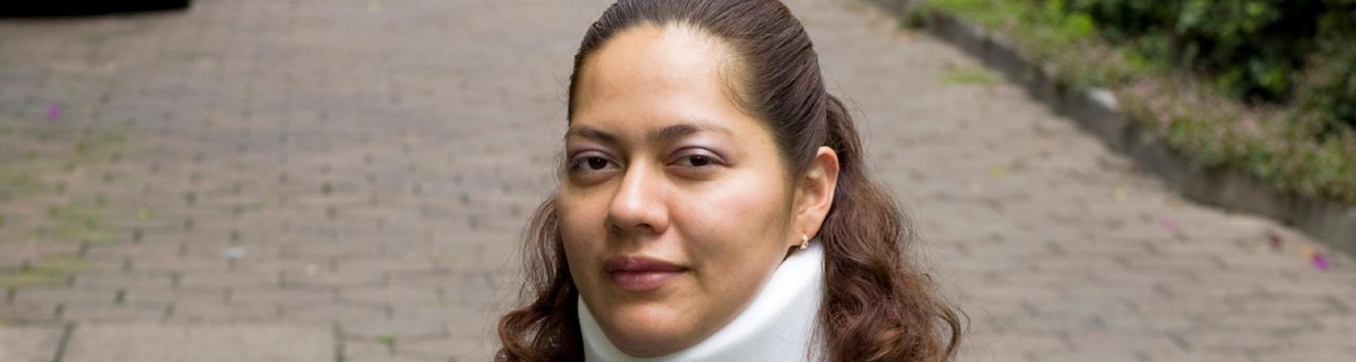 Vrouw zit in rolstoel met een nekbrace om